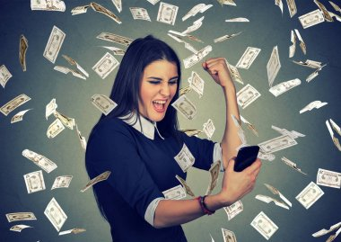 Woman using smart phone under money rain dollars falling down