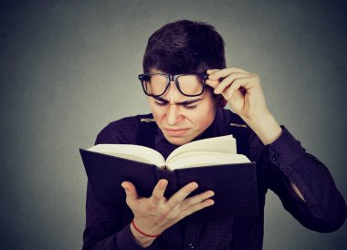 Closeup young man with eye glasses trying to read book, having difficulties seeing text, has sight problems. Eyesight issues concept. Human face expression stock vector
