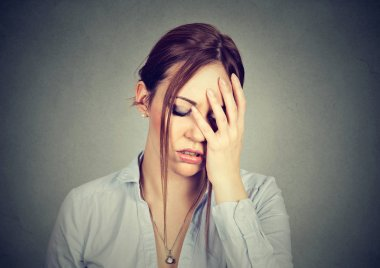 sad woman with worried stressed face expression looking down