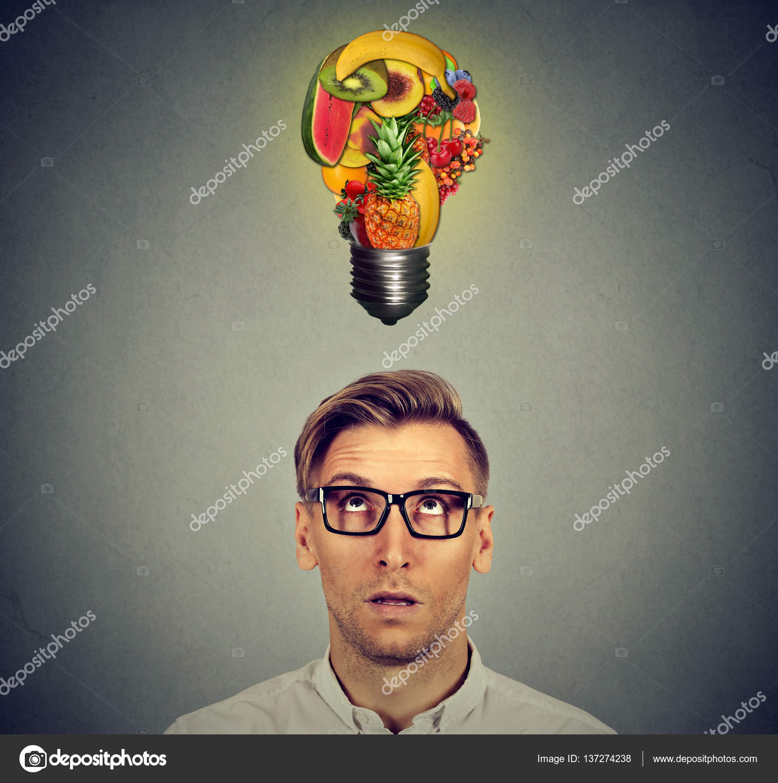eating healthy man looking up at fruit light bulb stock photo