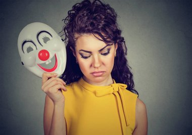 Sad woman taking off clown mask expressing cheerfulness