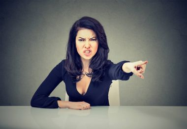 Angry business woman sitting at her desk and screaming pointing with finger to get out