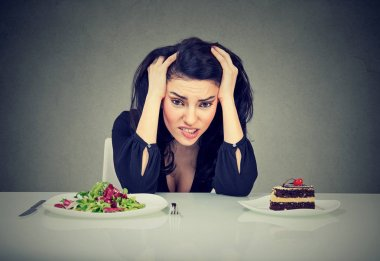 Woman tired of diet restrictions deciding to eat healthy food or cake she is craving