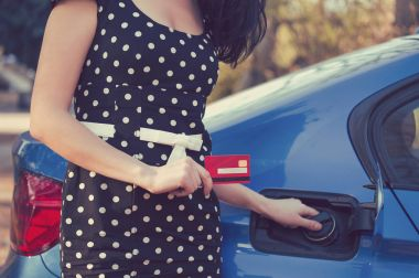Closeup of a woman with credit card opening fuel tank of a car