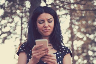 Angry woman looking at her mobile phone