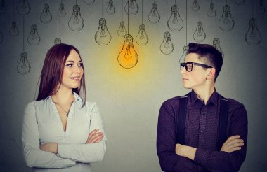 Cognitive skills concept, male vs female. Man and woman looking at light bulb