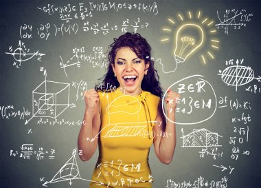excited student with idea light bulb and maths and science formulas on blackboard