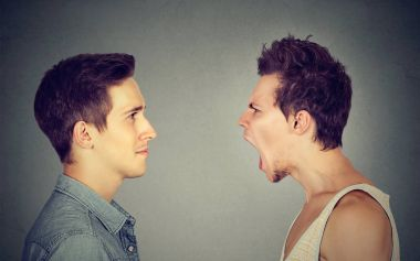 Side profile portrait of young angry man screaming at a calm smiling guy