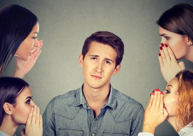 women whispering a secret latest gossip to a bored annoyed man
