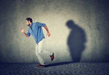 Man running away from his sad gloomy fat shadow on the wall