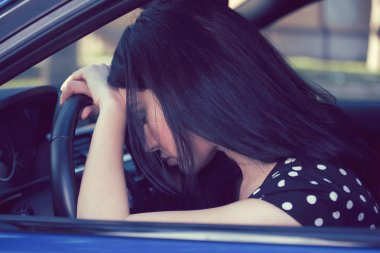 depressed woman driver sitting inside her car