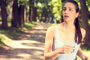 Sporty woman jogging in the park in sunrise light