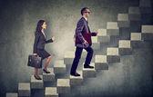 üzleti nő és férfi a táska segítségével fokozza a karrier-létrán lépcső