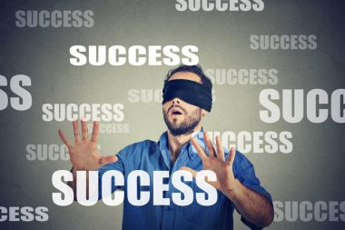 Blindfolded business man looking for success