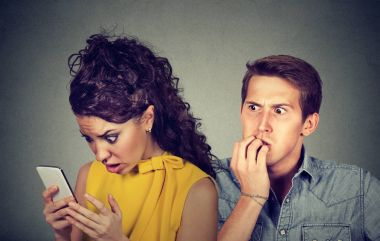 Cheating boyfriend. Man nervously biting fingernails while shocked girlfriend reading text messages on his mobile phone