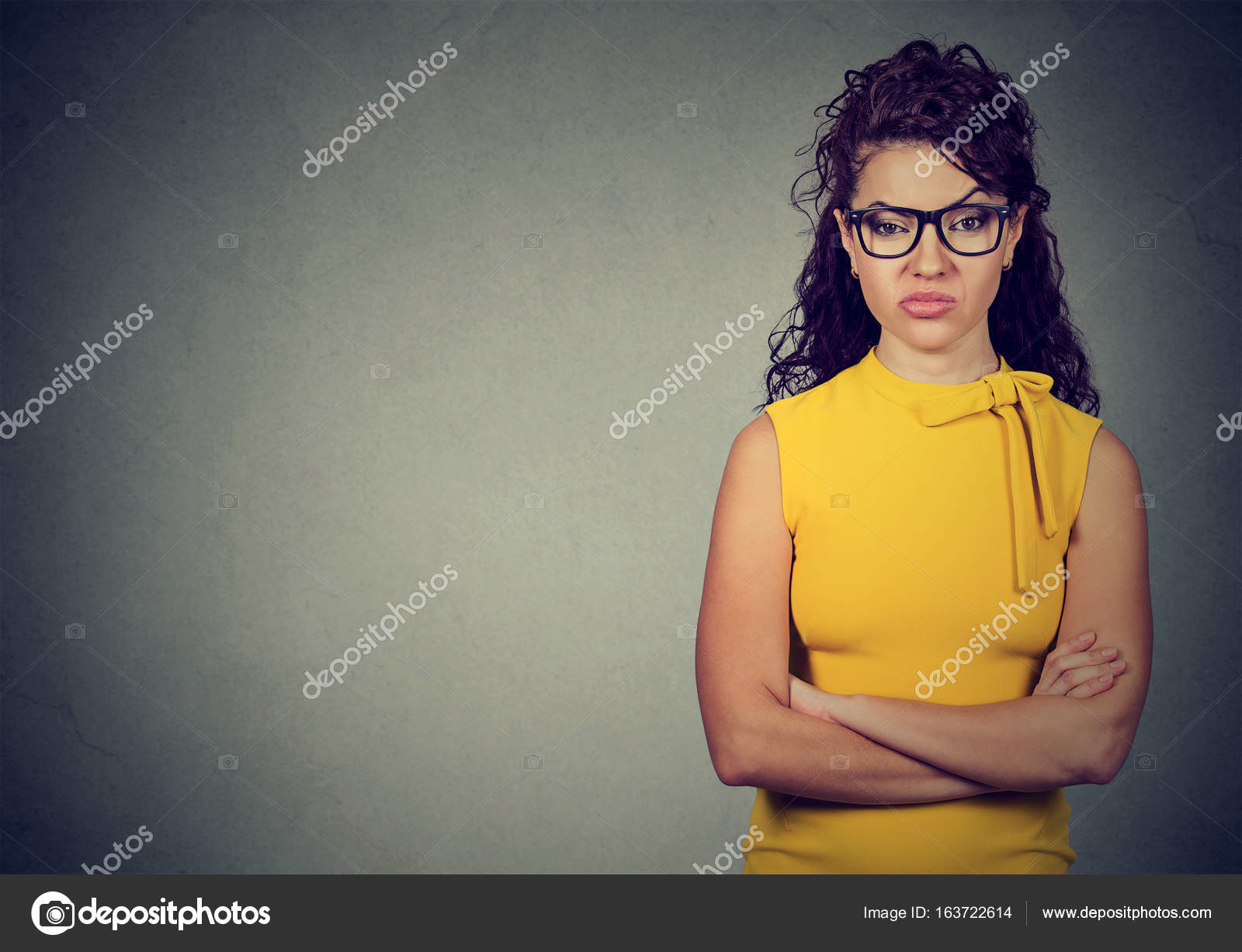Porträt von böse Frau im gelben Kleid Stand mit verschränkten Armen ...