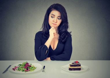 Dieting concept, beautiful woman choosing between healthy food and tasty cake