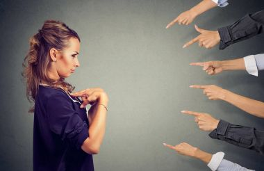 Blaming you. Anxious angry woman judged by different people pointing fingers hands at her.