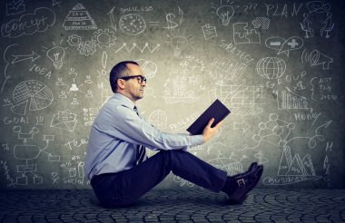 Man reading a book on a background with science formulas