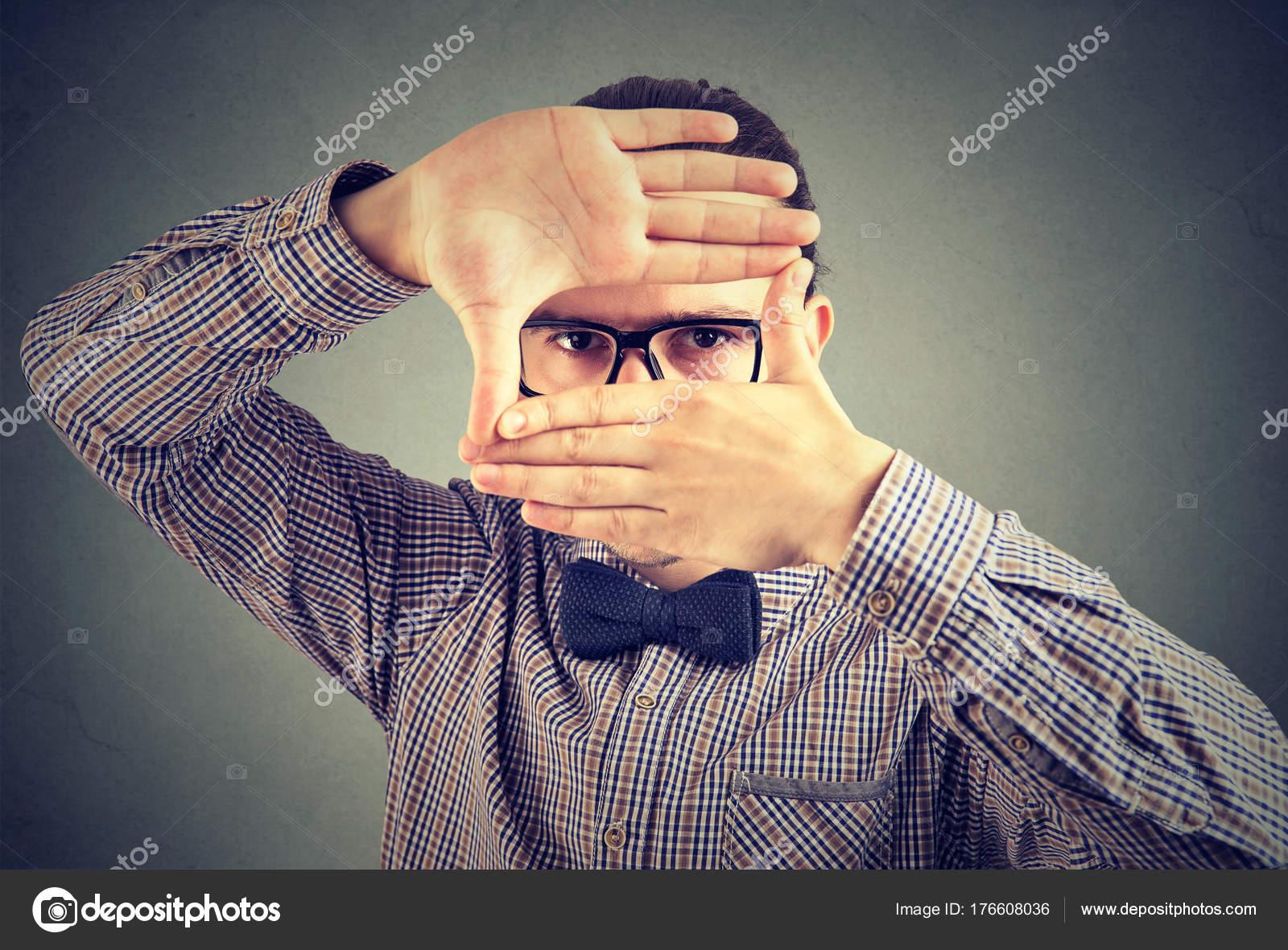 Ernster junger Mann macht ein Frame mit seinen Händen, Blick in die ...