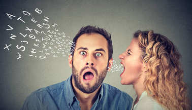 Angry woman screaming something in the ear of a shocked, scared guy