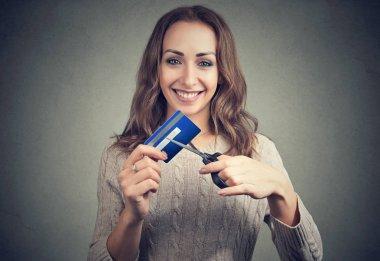 Happy woman cutting credit card