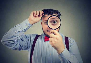 Interested man looking through magnifier