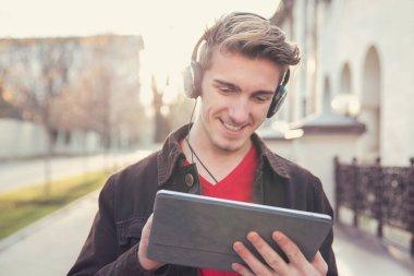 Handsome man using tablet outside