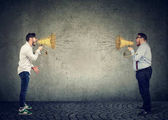 Fotografie Business men screaming into a megaphone at each other