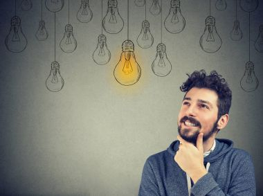 thinking man smiling looking up at light idea bulb above head