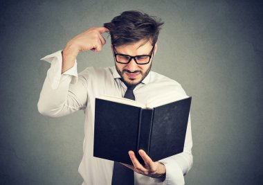 Puzzled man with book on gray