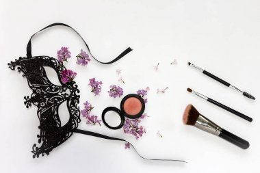 A composition of a masquerade black mask, spring flowers and cosmetics on a white background. Purple flowers are scattered randomly. Concept image