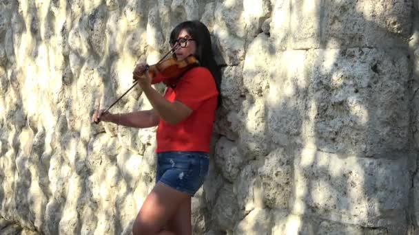 Nő játszik hegedű a szabadban.