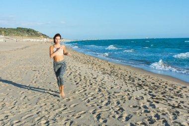girl runs on beach at sunset.