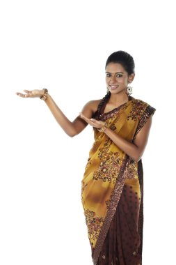 Woman in sari smiling with welcoming hand gesture
