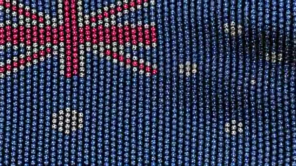 Flag of Australia, consisting of many soccer balls fluttering in the wind, on a black screen. Seamless looping video.