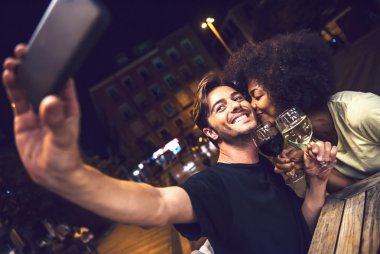 Casual interracial couple drinking wine during date and taking a