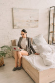 attractive businesswoman in blazer over pajamas using laptop while sitting on bed