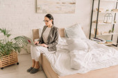 Fotografie young businesswoman in blazer over pajamas using laptop while sitting on bed