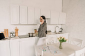 businesswoman in blazer over pajamas talking on smartphone while cooking in kitchen near table with tulips and documents