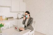 businesswoman in medical mask and blazer over pajamas working in kitchen, talking on smartphone and typing on laptop