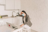 tired businesswoman in blazer over pajamas, medical mask and headset sitting near laptop while working at home