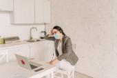 unavená podnikatelka v saku přes pyžamo, lékařskou masku a sluchátka sedí u notebooku při práci doma