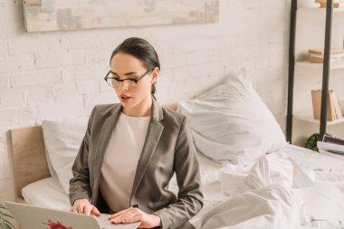 Beautiful businesswoman in blazer over pajamas using laptop in bedroom stock vector