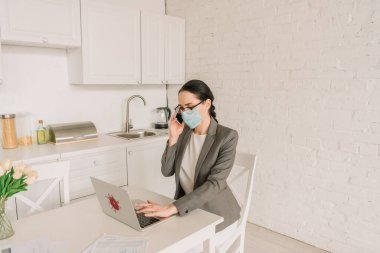 Businesswoman in medical mask and blazer over pajamas working in kitchen, talking on smartphone and typing on laptop stock vector