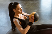 Fotografie Sportswoman holding ball and doing abs in sports center