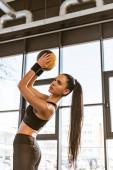 Krásná sportovkyně ve sportovním oblečení držení míč v tělocvičně
