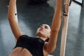 Fotografie Sportswoman in sports top lying on sport equipment in gym