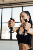 Photo Selective focus of sportswoman holding dumbbells with outstretched hands in gym