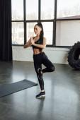 Sportovkyně se zaťatýma rukama pracuje v blízkosti fitness rohože v tělocvičně